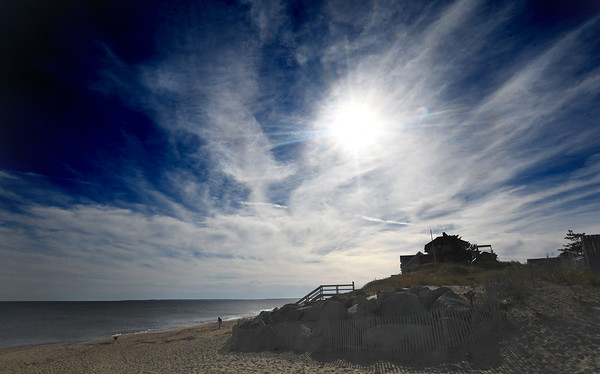 JIM VAIKNORAS/Staff photo The sun shines through cirrus clouds over Bennett Hill on Plum Island Thursday afternoon.