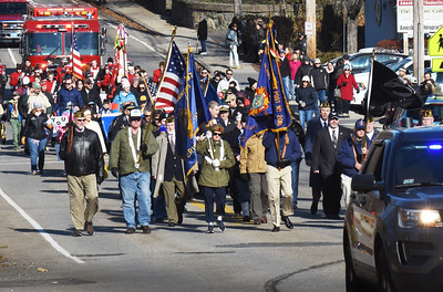 BRYAN EATON/Staff photo. With a police escort, Amesbury's Veterans Day parade heads down Main Street to the Doughboy Monument in front of the middle school.