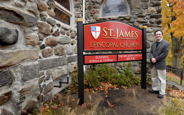 BRYAN EATON/Staff photo. Fr. John Satula  shows off St. James Episcopal Church's new sign on Main Street in Amesbury. The sign, which has been in the works for awhile, replaces a smaller one on the  front of the building, which can be obscured by a tree to passersby, and it's hoped the new sign will give more visibility.