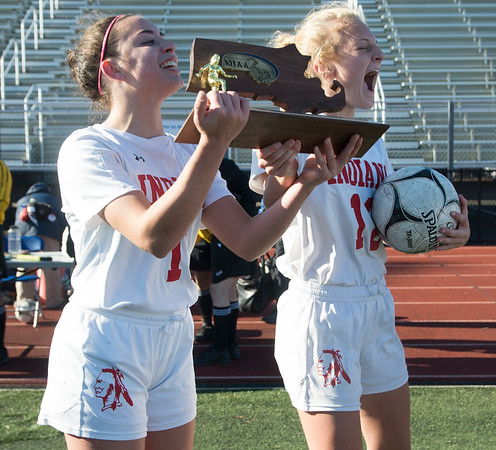 JIM VAIKNORAS/photo Amesbury High soccer captain's Emma DiPietro and Chelsea Lynch with their North Sectional Championship trophy at Manning Field in Lynn Sunday. Amesbury defeated Manchester-Essex  2-1 in double overtime.