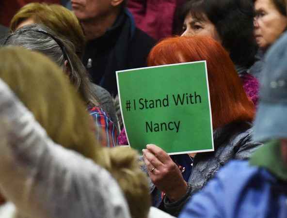 BRYAN EATON/Staff photo. Many in the audience of Congressman Seth Moulton's town hall meeting held signs of support for presumed house speaker Nancy Pelosi.
