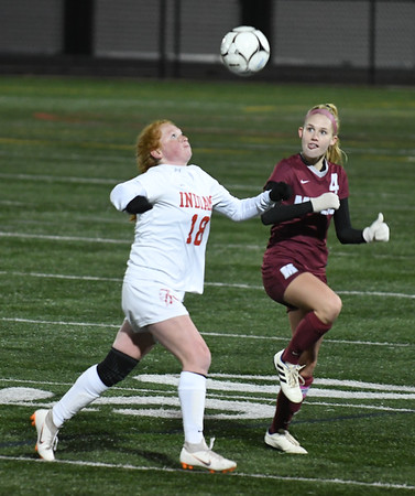 JIM VAIKNORAS/photo Amesbury's Gracie Doherty goes up for a header with Millis player Jessica Krauss during their state semi-final game at Mansfield High School Wednesday. Amesbury lost the game 2-1.