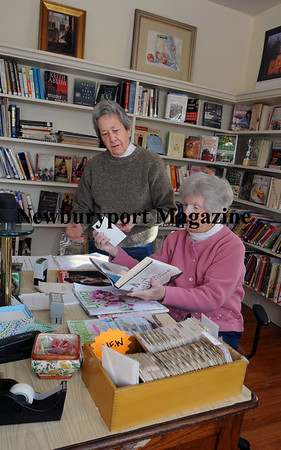 Volunteers Jody Axelson, left, and Lorraine Leary process returned books to be reshelved. Photo by Bryan Eaton