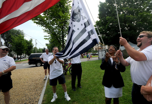 Newburyport: Yankee Homecoming Chairwoman Kathleen Bailey raises the Homecoming flag with some help from past chairmen Dennis Palazzo and Jason Lacroix at Olde Fashioned Sunday on the Mall Sunday. Jim Vaiknoras/Staff photo