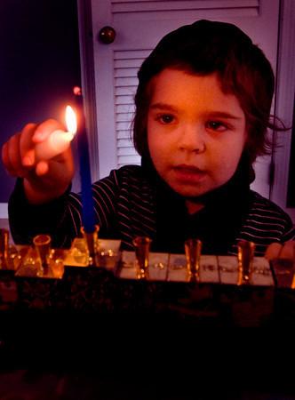 Judah Poupko 3, lights his menorah at his Newburyport home. Jim Vaiknoras/staff photo