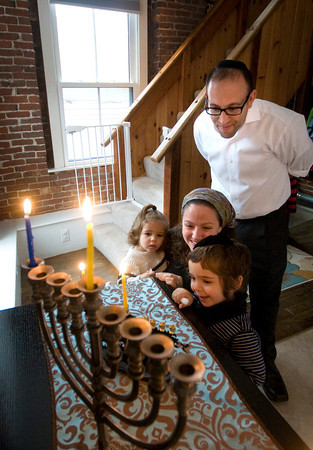 Rabbi Avi Poupko along with his wife Carina and sons Moses ,1, and Judah 3, light the menorah at their Newburyport home. Jim Vaiknoras/staff photo