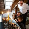 Rabbi Avi Poupko along with his wife Carina and sons Moses ,1, and Judah 3, light the menorah at their Newburyport home. Jim Vaiknoras/staff photo