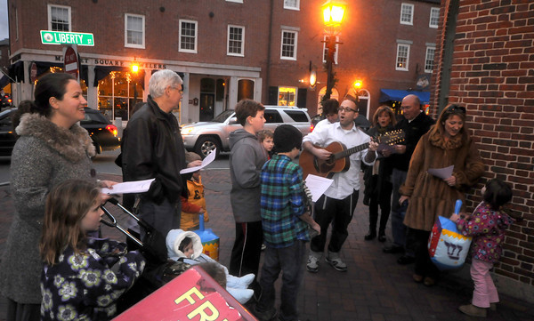 Newburyport: Rabbi Avi Poupko of the Congregation Ahavas Achim leads the first Chanukah Caroling on the corner of Librerty and State Streets in  Newburyport Thursday night. Along with singing at different location downtown the group passed out gelt, chocolate coins, to those who came to listen.JIm Vaiknoras/staff photo<br /> d, Newburyport: Rabbi Avi Poupko of the Congregation Ahavas Achim leads the first Chanukah Caroling on the corner of Librerty and State Streets in  Newburyport Thursday night. Along with singing at different location downtown the group passed out gelt, chocolate coins, to those who came to listen.JIm Vaiknoras/staff photo<br /> d