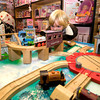 Max Tangen 2, who is visiting his Aunt plays with the wooden trains at the Dragons Nest in Newburyport.