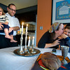 Rabbi Avi Poupko holds son Moses as Carina kisses son Judah after lighting the Shabbot candles. Shabbat is observed from 18 minutes before sunset on Friday evening until the appearance of three stars in the sky on Saturday night.
