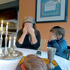 Carina Poupko and son Judah cover their eyes as they recite a blessing after lighting the Shabbot candles. Shabbat is observed from 18 minutes before sunset on Friday evening until the appearance of three stars in the sky on Saturday night.