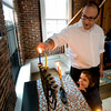 Rabbi Avi Poupko gets some help from his son Judah, 3, lighting the menorah a their Newburyport home. Jim Vaiknoras/staff photo