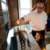 Rabbi Avi Poupko gets some help from his son Judah, 3, lighting the menorah a their Newburyport home. Jim Vaiknoras/staff photo