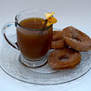 A cup of cider with a cinnamon and orange peel along with cider donuts.