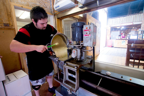 Amesbury's Cyrus Nguyen pours donut batter into the donut machine at Cider Hill Farm , Cyrus has been working at the farm for 2 years and has been making donuts for the past year.