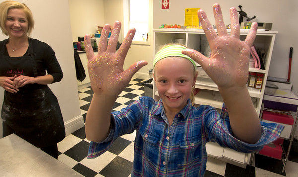 Hilary Larson laughs as Avery Keller, 9, shows off her edible disco glitter covered handsnduring a birthday party at Eat Cake in Newburyport.