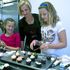 Hilary Larson helps out Molly Page , 10, and Sydney Turner, 9, at a party at Eat Cake in Newburyport.