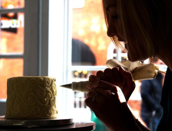 Hilary Larsondecortes a cake at her shop Eat Cake