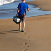 JIM VAIKNORAS/Staff photo Grady Booth, 7, carries his tackle box as he heads out to fish on the beach on Plum Island.