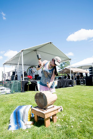 JIM VAIKNORAS/Staff photo Jen Boisvert carves a block of wood at the Fourth annual Byfield Music and Arts Festival at Manter Field in Byfield Saturday.