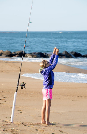 JIM VAIKNORAS/Staff photo  Maddie Modini,9, baits her line on the beach on Plum Island.