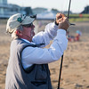 JIM VAIKNORAS/Staff photo  Earl Pacella baits his lineon the beach on Plum Island.