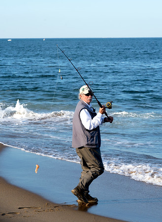 JIM VAIKNORAS/Staff photo  Earl Pacella casts his line the beach on Plum Island.