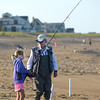 JIM VAIKNORAS/Staff photo Maddie Modini , 9, and her Grandfather Earl Pacella fish on the beach on Plum Island.