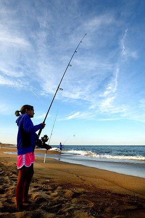 JIM VAIKNORAS/Staff photo Maddie Modini , 9, fishes on the beach on Plum Island.