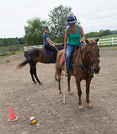 JIM VAIKNORAS/Staff photo Ellen Rukowicz of Newbury and Samantha Lucy during a polo class at Stage Hill Farm in Newbury.