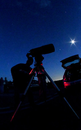 JIM VAIKNORAS/Staff Dan Smoody looks up at the moon at North Shore Amateur Astronomy Club (NSAAC) star party at Salisbury Beach Reservation. Jupiter can be seen to the left of the moon.