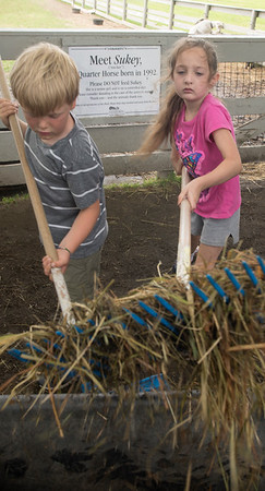 JIM VAIKNORAS/Staff photo, Griffin Dardinski and  Rose Hammond shovel hay at the Spencer-Peirce-Little Farm during the Little Farmers Camp.