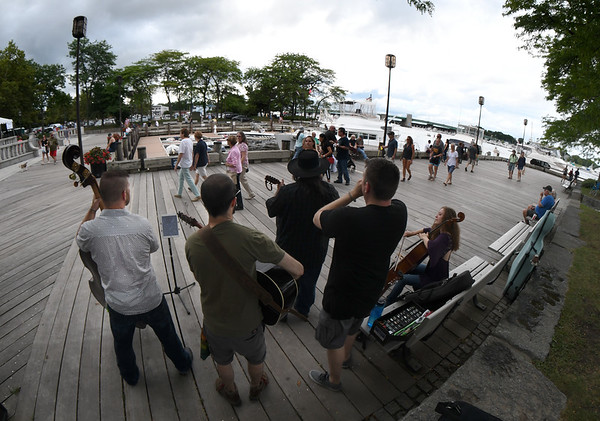 JIM VAIKNORAS/Staff photo people stream past as Two Weeks From Everywhere perform at the board walk in Newburyport.