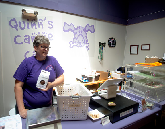 JIM VAIKNORAS/Staff photo Owner Quinn Soine-Norris with a bag of liver treats at Quinn's Canine Cafe in Newburyport.