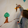 JIM VAIKNORAS/Staff photo Olivia Powell , 5, adds an eagle to a mural at the Parker River Earth Day Festival.