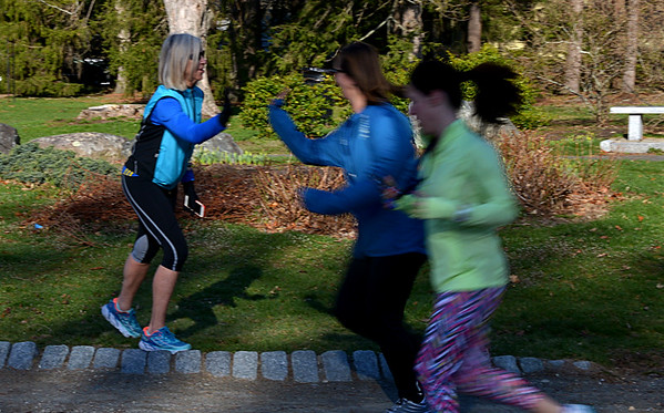JIM VAIKNORAS/Staff photo Nancy McCarthy high fives her runners during  an early morning Couch to 5K workout at Atkinson Common in Newburyport.