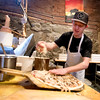 JIM VAIKNORAS/Staff photo Patrick Lucier covers a pizza with cheese at Flatbreads in Amesbury.