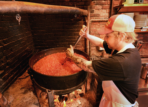 BRYAN EATON/Staff photo. Randy Mason who has been with Flatbreads for a year, stirs the tomato sauce in a cauldron over an open fire.