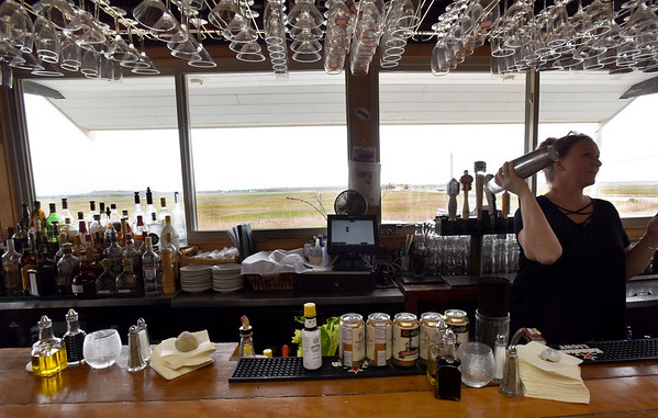 BRYAN EATON/Staff photo. Amy D'Amato at the bar of the Plum Island Grill's enclosed deck with views of the Great Marsh.