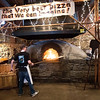 JIM VAIKNORAS/Staff photo Patrick Lucier slides a pizza in teh wood fired oven at Flatbreads in Amesbury.