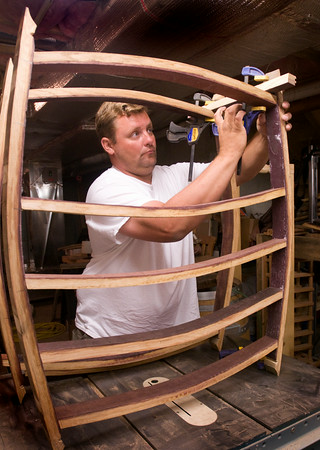 Chris clamps together pieces of wood for a wine rack.