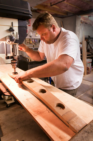 Chris drills depressions into a stave which will be a tea light candle holder.