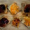 JIM VAIKNORAS/Staff photo Fig Chutney, Orange Marmalade, and Hot Pepper Jelly on sea salt crackers .