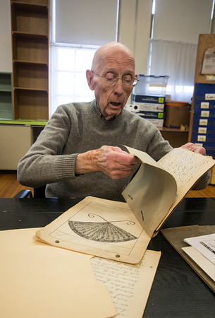 John Gove looks over his penmenship book he saved from hios time at the Brown School in the 1930's