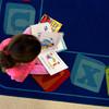 Skylar Ikemoto reads a book in Melissa Duguie's kindergaten class