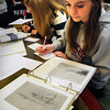 Newburyport: Mika Phipps, 14, right, looks at old photographs of the Newburyport waterfront while Sydney Todd, 13, researches the Fire of 1811 which wiped out much of the business areas of Newburyport. They and other students from the River Valley Charter School were at the archival center at Newburyport Public Library on Tuesday learning about local history tying together people with their relationship to the Merrimack River. Bryan Eaton/Staff Photo