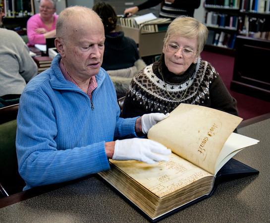 Sheryl and Bob Richard, Newburyport residents and NPL volunteers look through a Newburyport record book dated between 1764-1789.