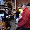 BRYAN EATON/Staff Photo. Hannah Ross with regular customer Jim Noyes of Newbury with a breakfast sandwich and coffee.