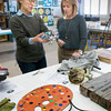BRYAN EATON/ Staff Photo. Sue Stasiuk, left, and Diane Doyle look over some of the donated objects for the art showing.