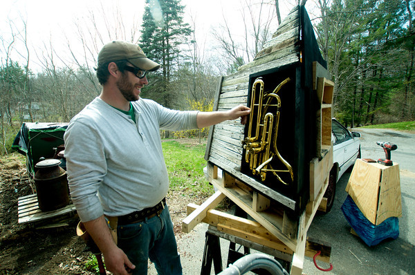 Artist Sean Bixby fits in a piece of a baritone horn into the Pentucket Arts project at his Merrimac home.
